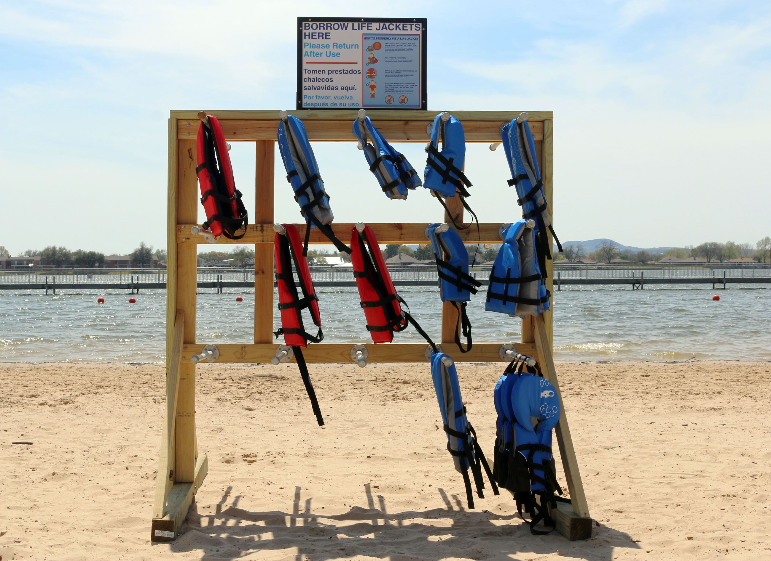 Wooden stand with lifejackets hanging on it on a beach.